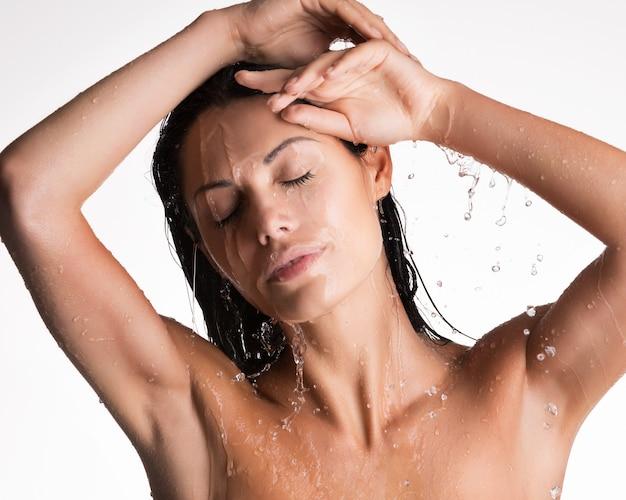 Rostro de una relajante mujer mojada en la ducha bajo el agua.