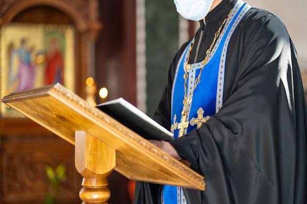 Sin rostro. el sacerdote lee un libro de oraciones durante el servicio del bautismo. tradiciones y rituales religiosos. fe cristiana