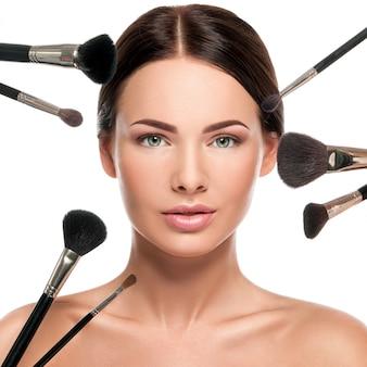 Rostros femeninos y pinceles de maquillaje