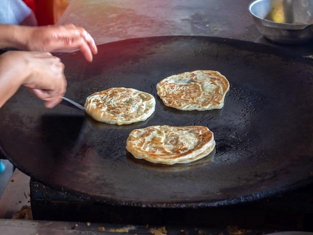 Roti making, roti y huevo frito en la sartén.