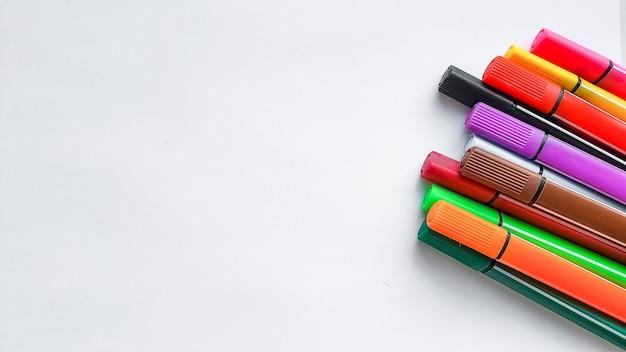 Rotuladores multicolores aislados en la pared blanca. arte, creatividad, hoja de papel. juego básico de rotuladores de colores. concepto de hobby. posibilidades de tiempo libre para quedarse en casa. lección de pintura.