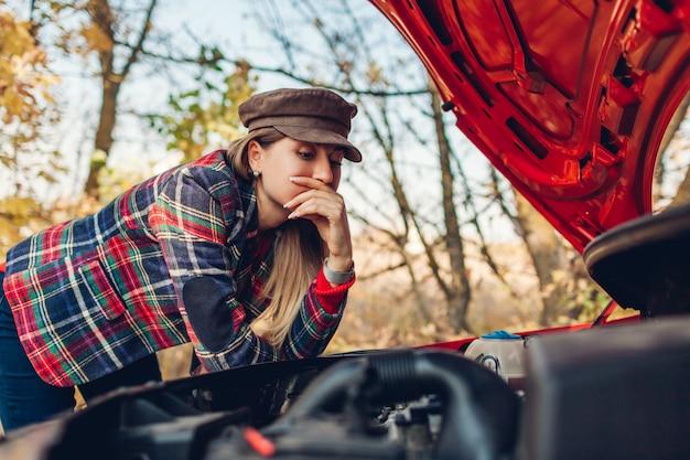 Rotura de automóvil. mujer confundida abrió el capó de su automóvil que se detuvo en la carretera y miró el engranaje del motor