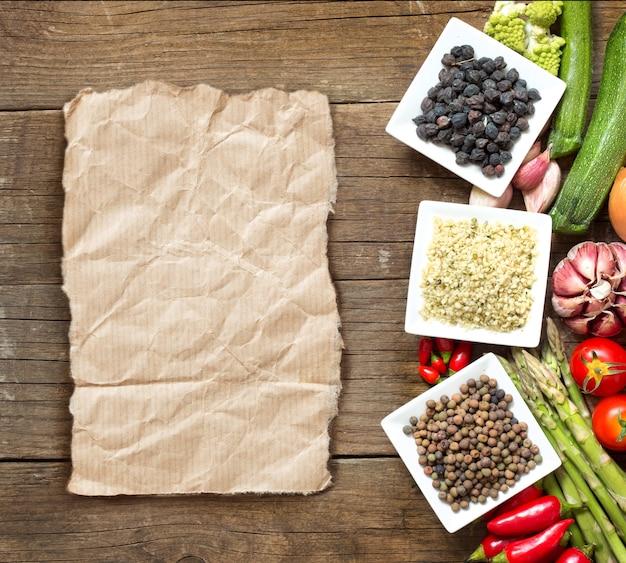 Roveja, semillas de cáñamo y garbanzos negros en cuencos y verduras en una mesa de madera vista superior con espacio de copia en papel