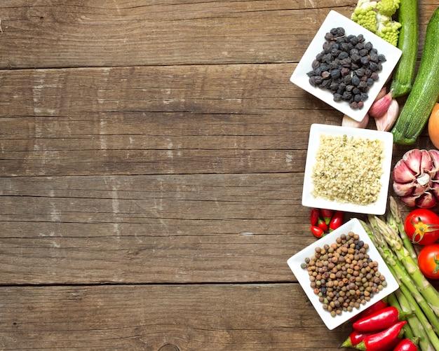 Roveja, semillas de cáñamo y garbanzos negros en cuencos y verduras en una mesa de madera vista superior con espacio de copia