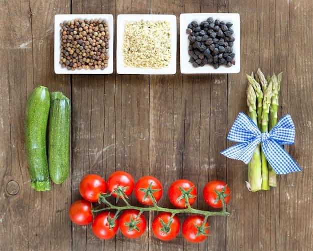 Roveja, semillas de cáñamo, garbanzos negros en cuencos y verduras en una mesa de madera vista superior