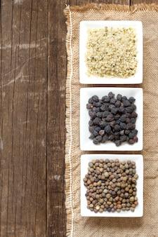 Roveja, semillas de cáñamo y garbanzos negros en tazones sobre una mesa de madera vista superior