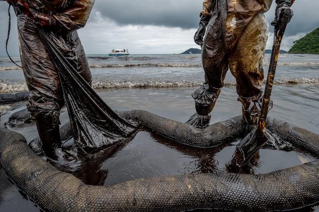 Royal thai navy y voluntarios locales que limpian una playa de una mancha de aceite en la playa de ao phrao en la isla de samed, rayong, tailandia.