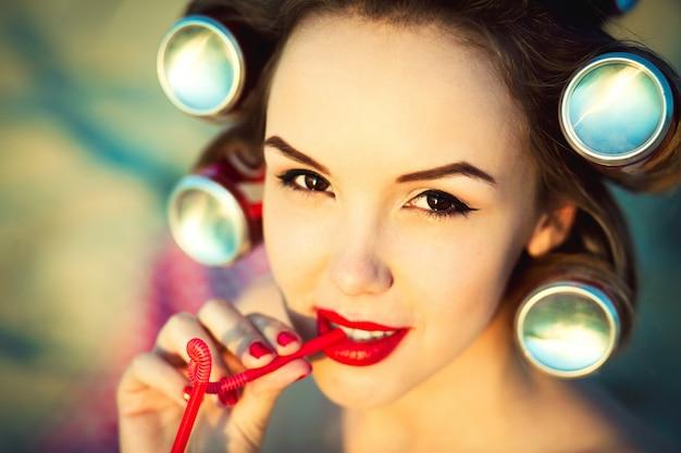 Rubia al estilo de los ochenta pin-up. lápiz labial rojo brillante y refresco