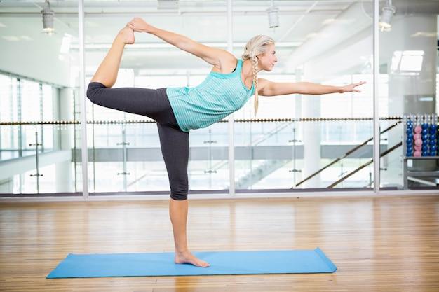 Rubia apta haciendo yoga en colchoneta en el estudio