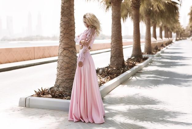 Rubia bien formada junto al mar en dubai, palmeras, vestidos hermosos y calientes, sesión de fotos de moda de estilo de vida soleado de verano, vestido ondeando en el viento, tranquilo y relajado cerca de la piscina, peinado, maquillaje