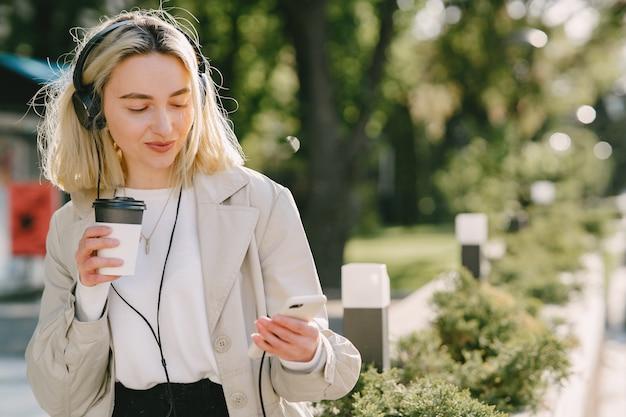 Rubia camina en la ciudad de verano con una taza de café