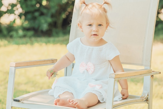 Rubia caucásica niña sentada en una silla en el jardín en verano. foto de alta calidad