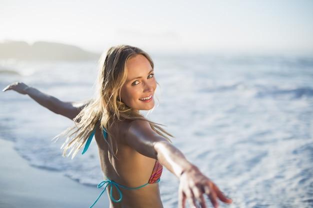 Rubia contenta de pie en la playa en bikini con los brazos extendidos.