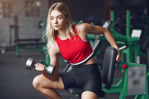 Rubia deportiva en un entrenamiento de ropa deportiva en un gimnasio