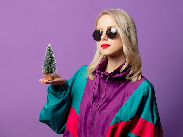 Rubia elegante en cazadora de los años 80 y gafas de sol redondas con árbol de navidad en la pared púrpura