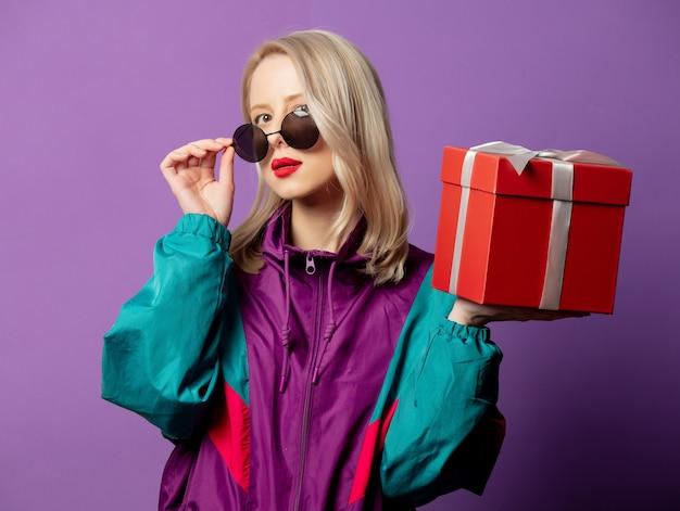 Rubia elegante en cazadora de los años 80 y gafas de sol redondas con caja de regalo en la pared púrpura