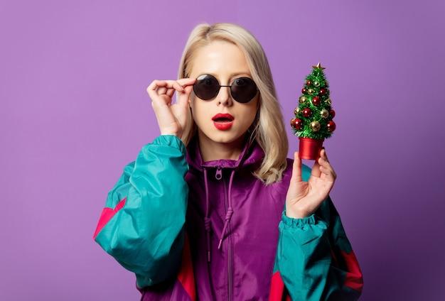 Rubia elegante en cazadora de los años 80 y gafas de sol roud sostiene el árbol de navidad en la pared púrpura