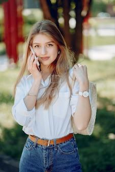 Rubia elegante en un parque de verano con teléfono