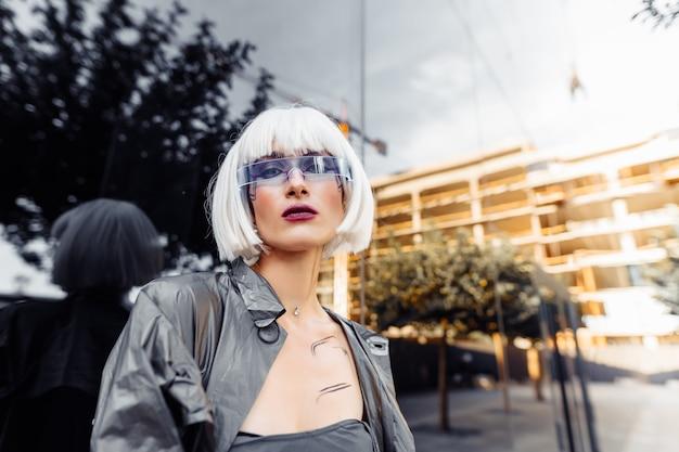 Rubia elegante con ropa futurista y gafas en un espejo.