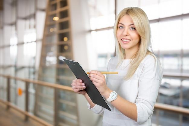 Rubia empresaria escribiendo notas en el portapapeles