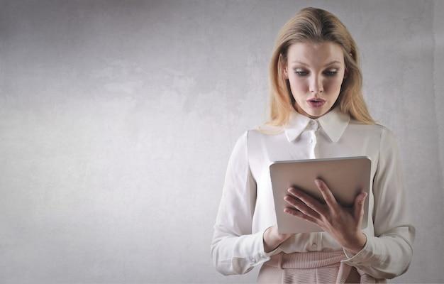 Rubia empresaria usando una tableta