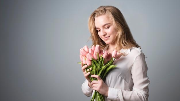 Rubia encantadora disfrutando de un ramo de flores