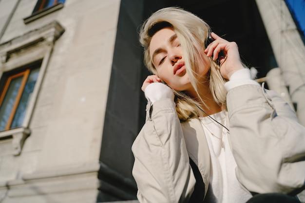 Rubia escucha música en una ciudad veraniega