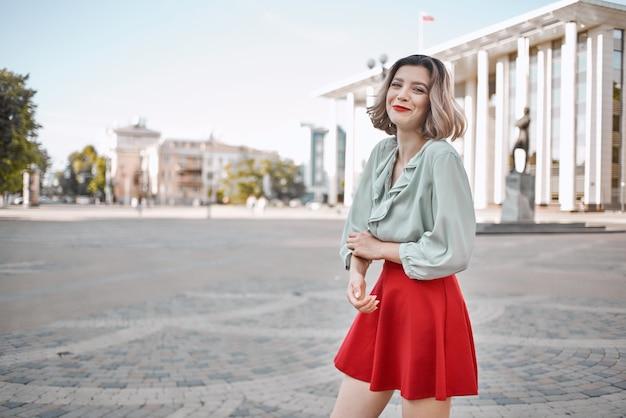 Rubia en falda roja al aire libre caminando al aire libre posando