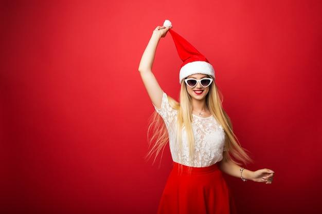 Rubia feliz con sombrero de santa sobre fondo rojo aislado. gafas de sol con montura blanca.