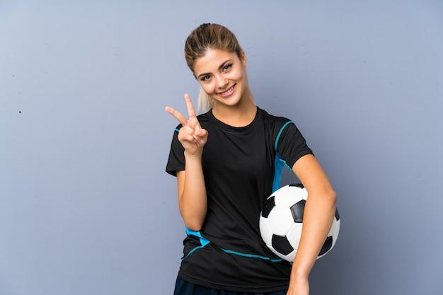 Rubia futbolista adolescente chica sobre pared gris sonriendo y mostrando el signo de la victoria