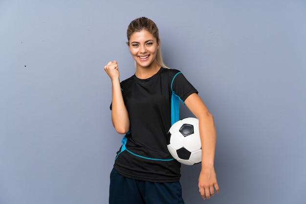 Rubia futbolista adolescente chica sobre pared gris