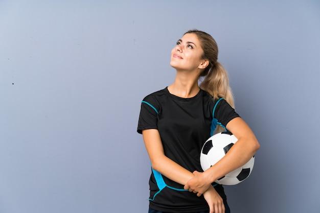 Rubia futbolista adolescente niña gris pared mirando hacia arriba mientras sonríe