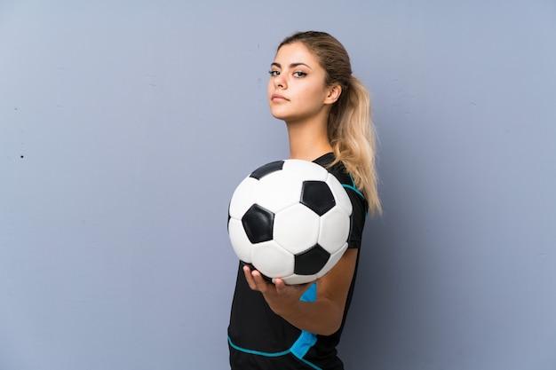 Rubia futbolista adolescente niña gris pared
