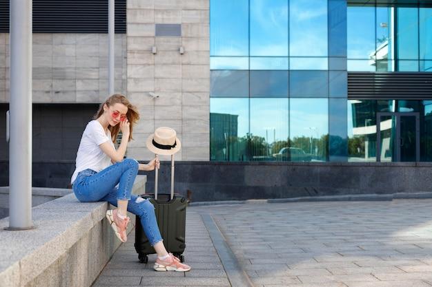 Rubia con gafas con maleta y sombrero se sienta cerca del aeropuerto en verano