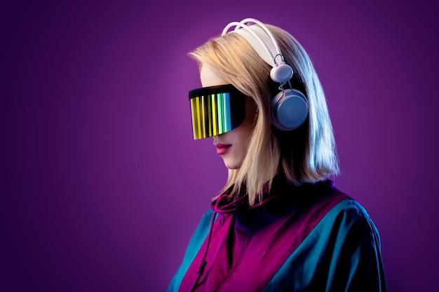 Rubia con gafas de realidad virtual y auriculares en pared rosa