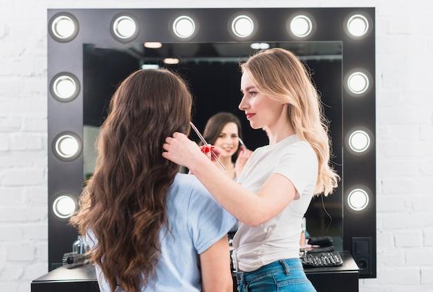 Rubia haciendo maquillaje de ojos para cliente con cepillo