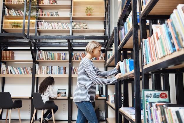 Rubia joven apuesta en camisa a rayas y jeans buscando un libro en el estante de la biblioteca, preparándose para los exámenes en la universidad