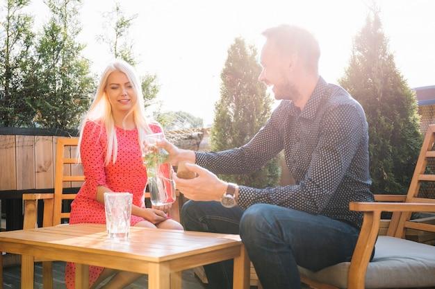 Rubia joven mirando a hombre sirviendo bebida en vidrio