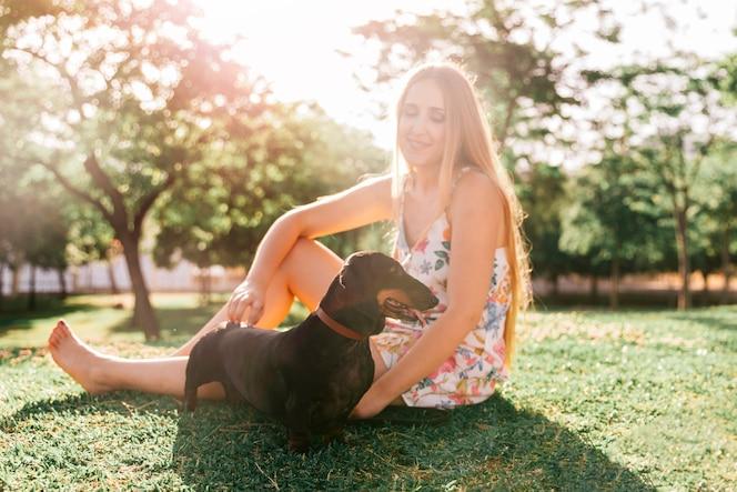 Rubia joven sentada con su perro en el parque