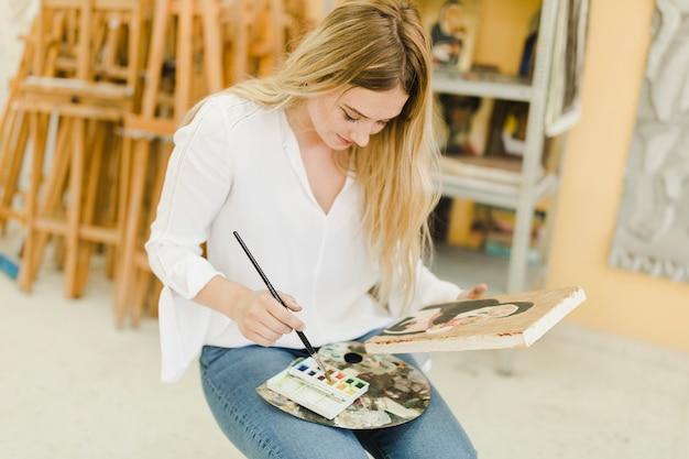 Rubia joven sentada en el taller de pintura con pincel