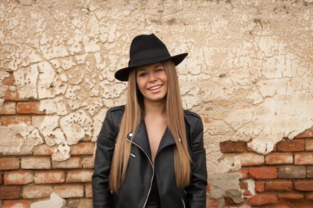 Rubia joven con sombrero negro guiñando un ojo