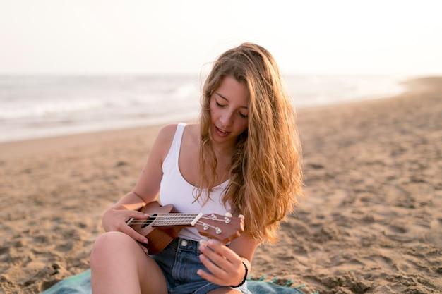 Rubia joven tocando el ukelele en la playa