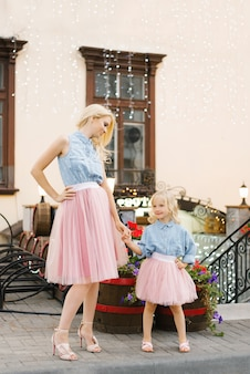 La rubia madre y su pequeña hija con faldas rosadas y camisas de mezclilla se agarran el cinturón al aire libre en la ciudad y se miran.