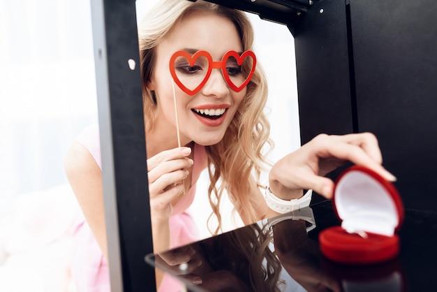 Rubia mira el anillo de bodas en una impresora 3d.