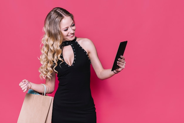 Rubia de moda con bolsa de papel tomando selfie
