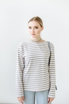 Rubia modelo de mujer mirando al frente en una escena blanca en el estudio