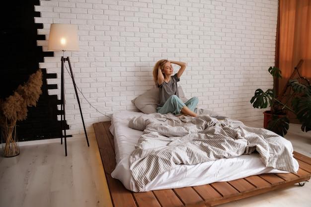 Rubia modelo en pijama en la cama por la mañana