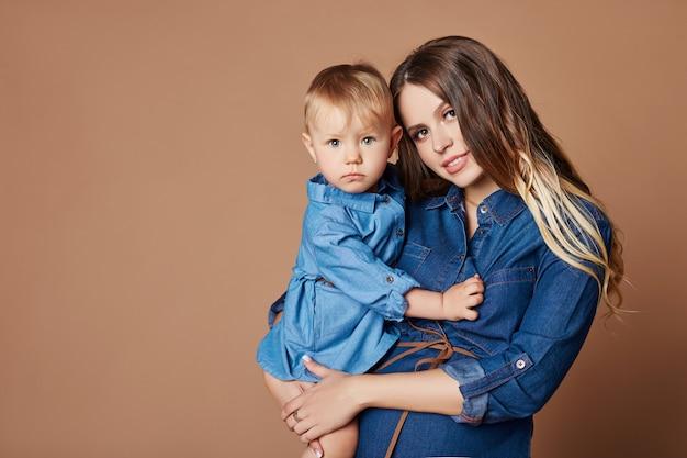 Rubia de la mujer embarazada del retrato de la moda con el niño