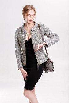 Rubia de mujer de negocios hermosa joven en vestido negro, chaqueta y bolso mira su reloj sobre fondo gris. la chica llega tarde a tiempo