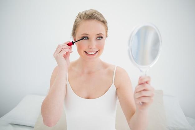 Rubia natural alegre con espejo y aplicación de rímel.